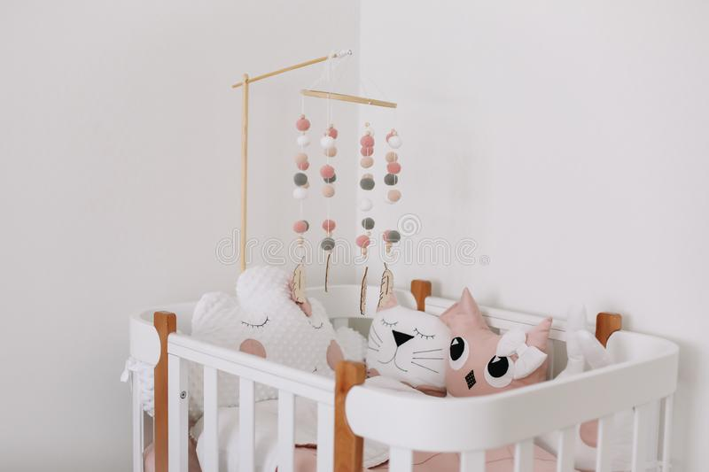 Beautiful interior of baby room. White crib with pillows and pink blanket in baby room.  pink bedding on bed against white wall royalty free stock photos