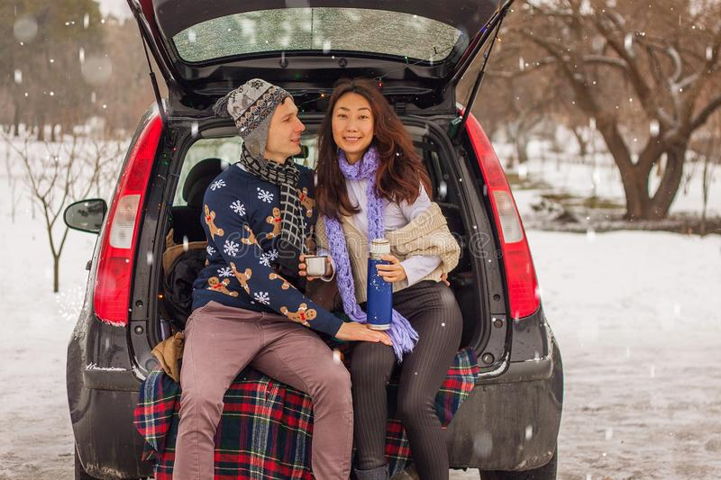 Beautiful international couple relaxing in nature in winter. Romantic meeting of a couple in love in the snow. Young couple sit in. Beautiful international stock images