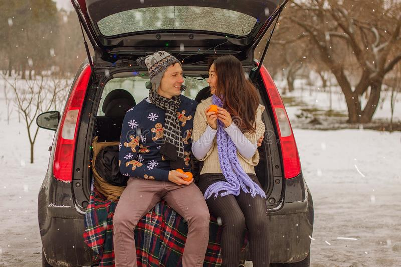 Beautiful international couple relaxing in nature in winter. Romantic meeting of a couple in love in the snow. Young couple sit in. Beautiful international stock image