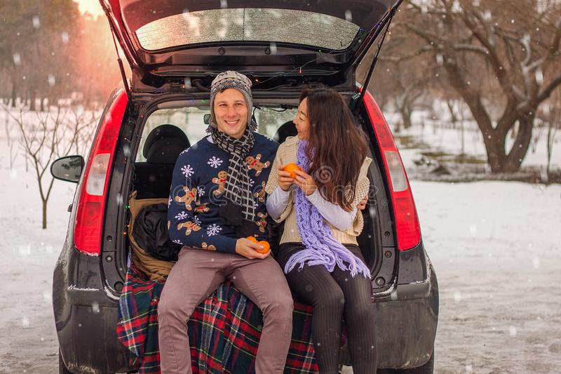 Beautiful international couple relaxing in nature in winter. Romantic meeting of a couple in love in the snow. Young couple sit in. Beautiful international royalty free stock photography