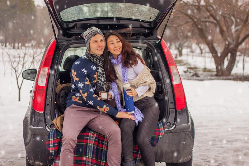 Beautiful international couple relaxing in nature in winter. Romantic meeting of a couple in love in the snow. Young couple sit in. Beautiful international royalty free stock image