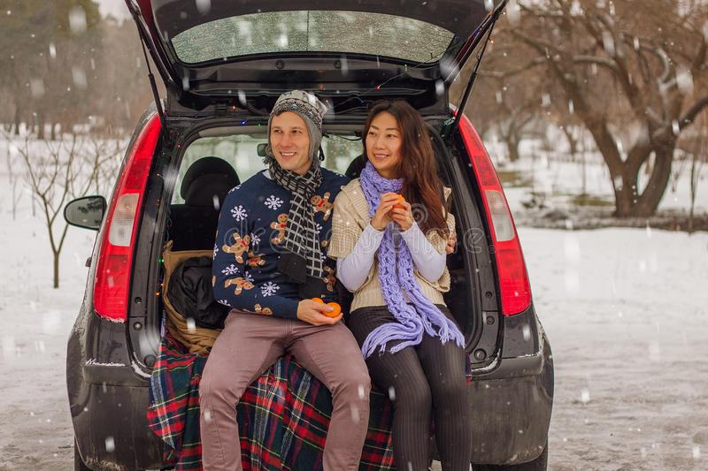 Beautiful international couple relaxing in nature in winter. Romantic meeting of a couple in love in the snow. Young couple sit in. Beautiful international stock photos