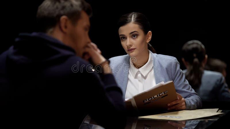 Beautiful interrogator meeting arrested man, investigating crime, mistrust. Stock photo royalty free stock photography