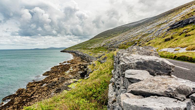 Beautiful Irish landscape with the sea and the rural coastal road along​​ the Burren. Geosite and geopark, Wild Atlantic Way, cloudy spring day royalty free stock images