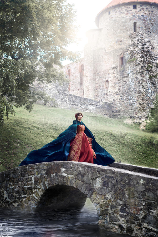 Beautiful Isabella of France, queen of England on Middle Ages period. In red gown near medieval castle royalty free stock image
