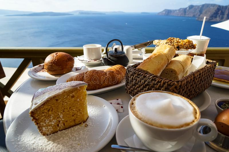 Beautiful island breakfast with Aegean sea view including cappuccino cup, cake, baguette, croissant, boiled egg, hot tea royalty free stock photos
