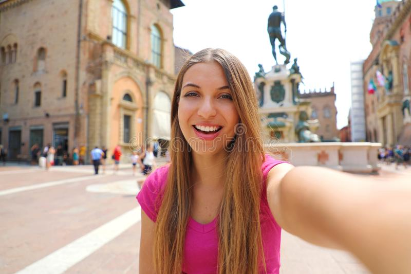 Beautiful Italy. Attractive smiling young woman take self portrait in Piazza del Nettuno square Bologna city, Italy royalty free stock photo