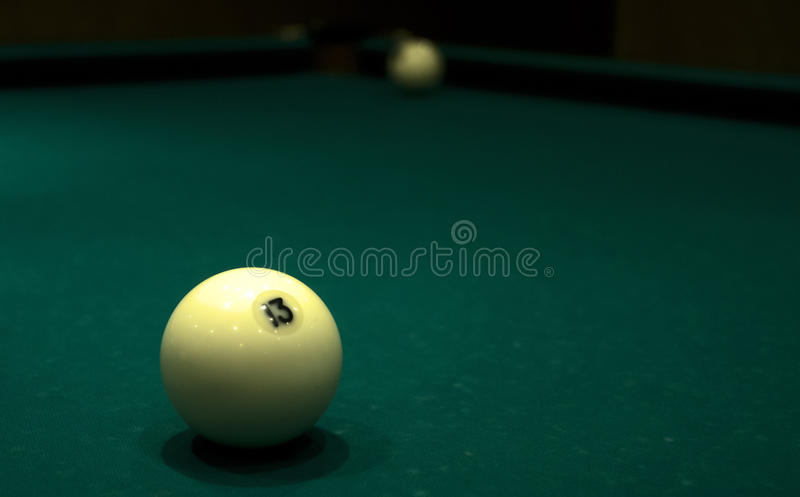 Beautiful ivory ball with the number 13 is on the table with a green cloth royalty free stock photography
