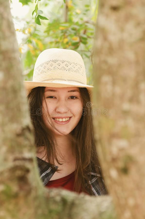 Beautiful japanese descendant woman on a nature scene. Portrait of a smiling woman wearing hat behind a tree trunk royalty free stock photos