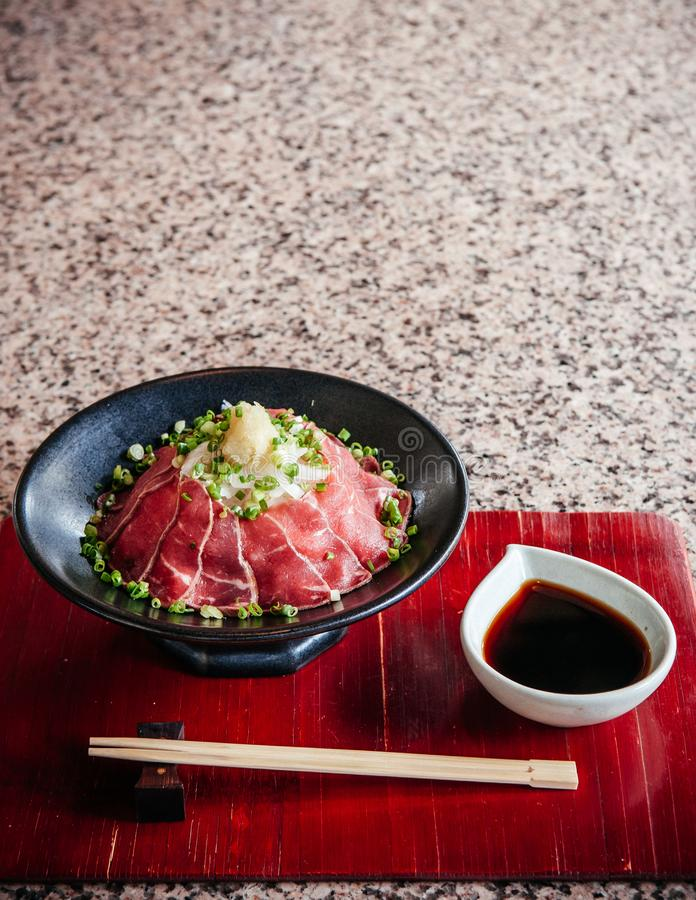 Japanese Tataki raw beef cuisine with ginger, onion, spring onion and soy sauce set on red wooden tray. Beautiful Japanese Tataki raw beef cuisine with ginger stock photography