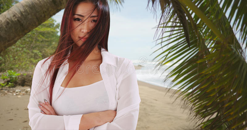 Beautiful Japanese woman standing at the beach smiling at camera royalty free stock images