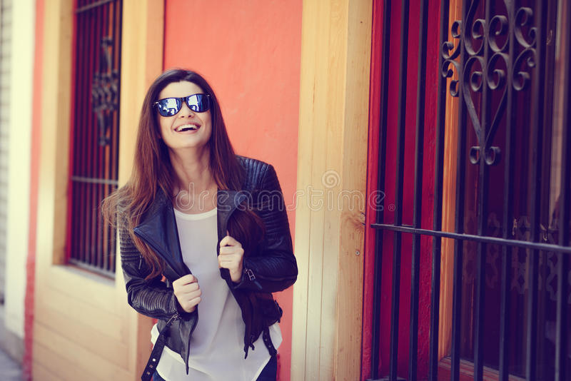 Beautiful japanese woman in urban background wearing leather jacket. Portrait of beautiful japanese woman laughing in urban background wearing leather jacket royalty free stock photography