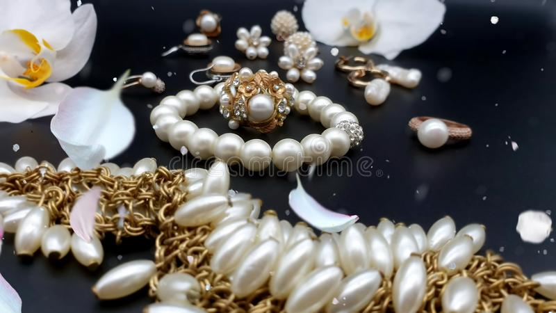 Beautiful jewelry white pearl  set  for woman and girl necklace earrings  bracelet   earring rings on black gold silver  backgroun. Beautiful jewelry white pearl stock images