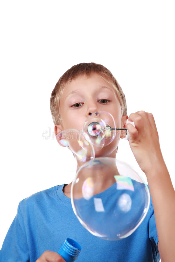 Beautiful joyful blond boy in a bright blue t-shirt blowing soap bubbles stock images
