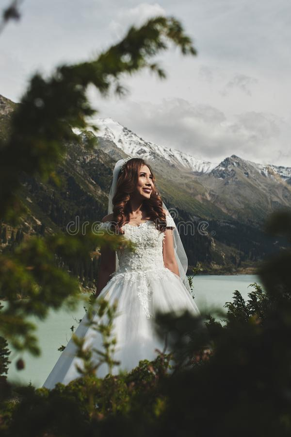 Beautiful Kazakh Asian bride in a white dress and veil against the backdrop of a lake in the mountains landscape, wedding photo royalty free stock photography