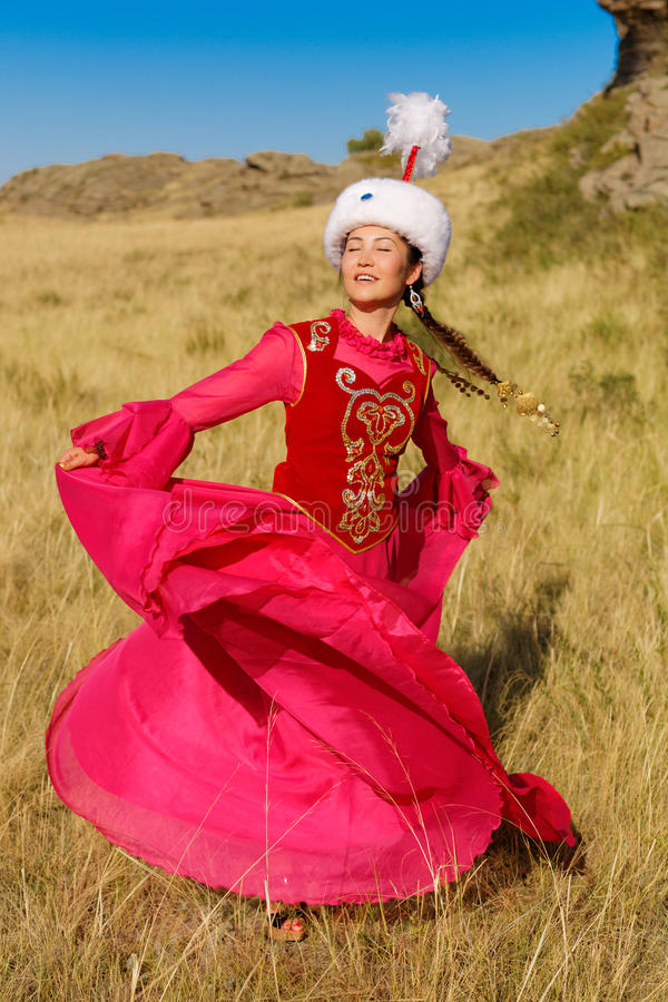 Beautiful kazakh woman and man in national costume. In the steppe dancing with dombyra royalty free stock photography