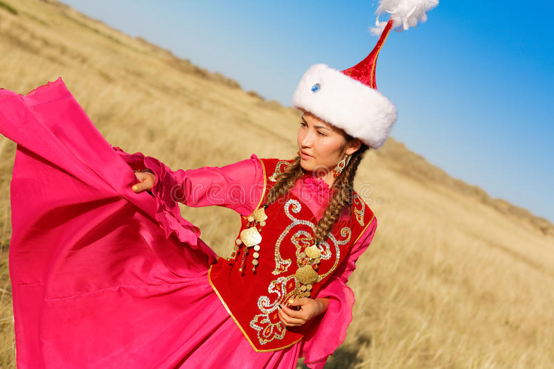 Beautiful kazakh woman and man in national costume. In the steppe dancing with dombyra stock photo