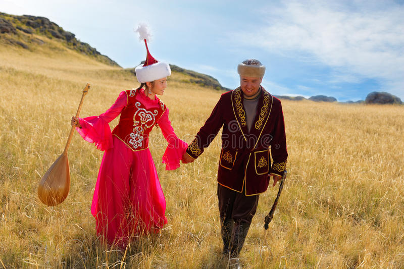 Beautiful kazakh woman and man in national costume. Beautiful kazakh women and men in national costume in the steppe dancing with dombyra stock image