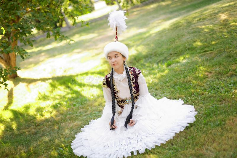 Beautiful kazakh woman in national costume. In summer park royalty free stock images