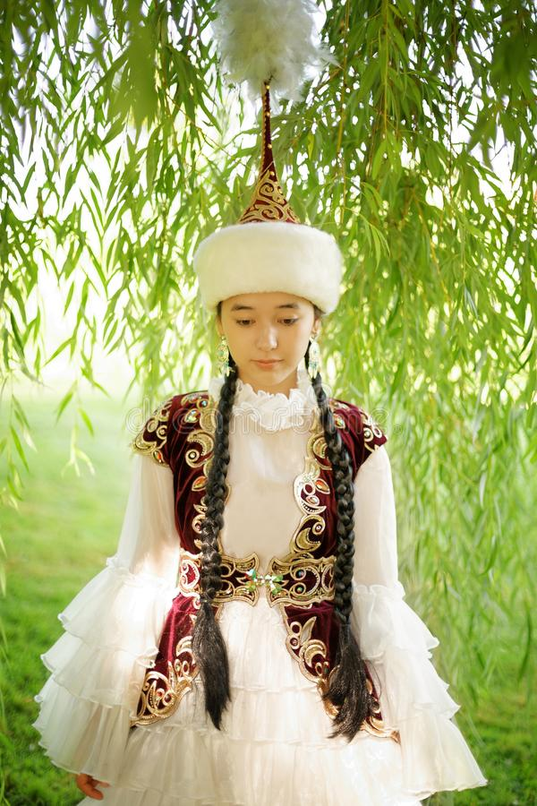 Beautiful kazakh woman in national costume. In summer park royalty free stock image