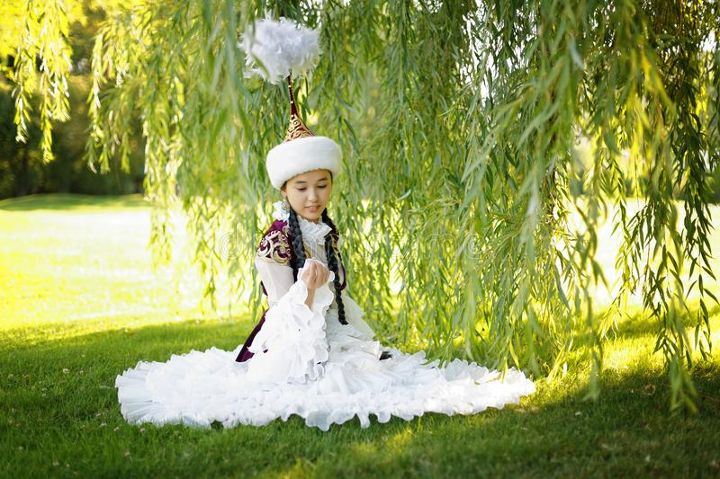 Beautiful kazakh woman in national costume. In summer park stock photo