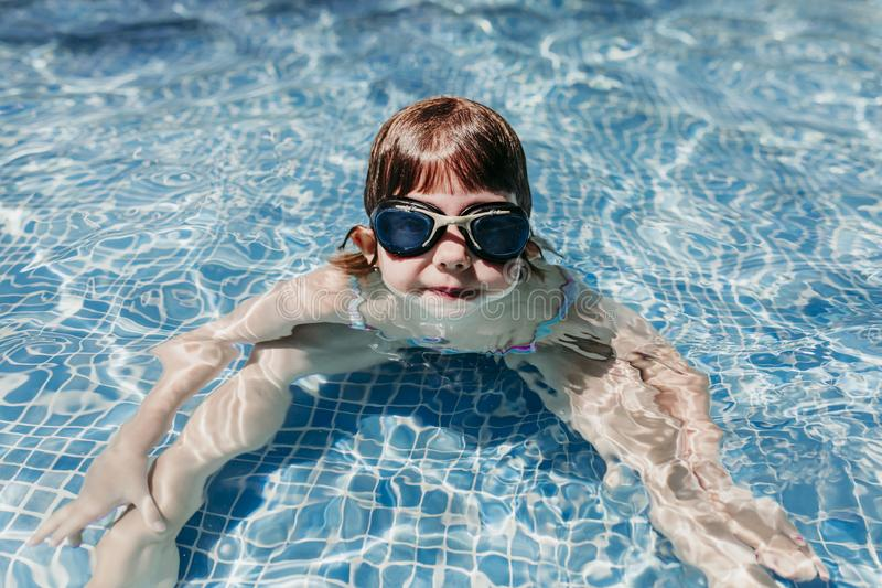 Beautiful kid girl at the pool diving with water goggles. fun outdoors. Summertime and lifestyle concept royalty free stock photos