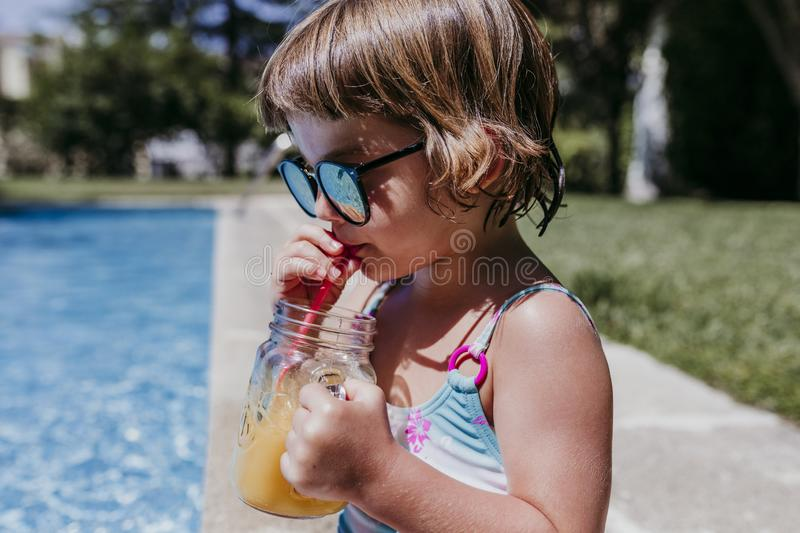 Beautiful kid girl at the pool drinking healthy orange juice and having fun outdoors. Summertime and lifestyle concept. Childhood, playful, blue, caucasian stock photos