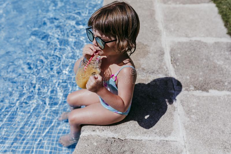 Beautiful kid girl at the pool drinking healthy orange juice and having fun outdoors. Summertime and lifestyle concept. Childhood, playful, blue, caucasian royalty free stock images