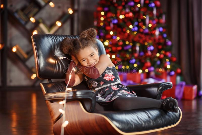 Beautiful kid girl 5-6 year old wearing stylish dress sitting in armchair over Christmas tree in room. Looking at camera. Holiday stock image