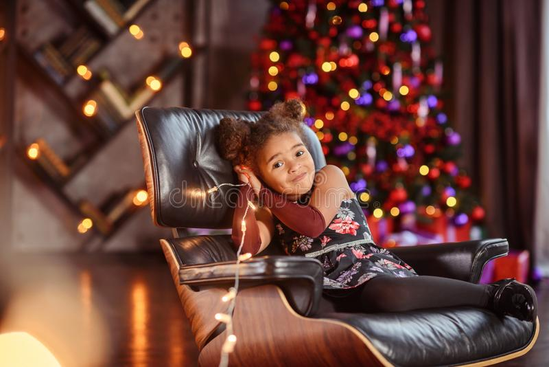 Beautiful kid girl 5-6 year old wearing stylish dress sitting in armchair over Christmas tree in room. Looking at camera. Holiday stock photo