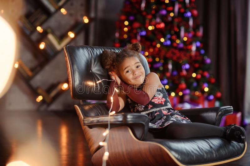Beautiful kid girl 5-6 year old wearing stylish dress sitting in armchair over Christmas tree in room. Looking at camera. Holiday. Cute little baby sitting in royalty free stock photos