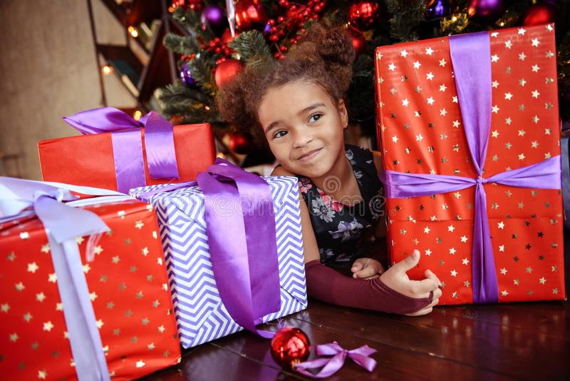 Beautiful kid girl 5-6 year old wearing stylish dress sitting in armchair over Christmas tree in room. Looking at camera. Holiday stock photos