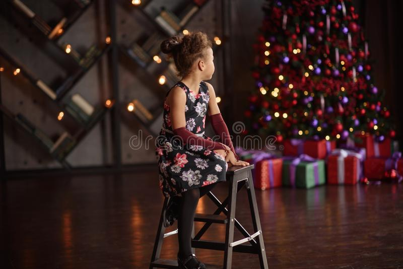Beautiful kid girl 5-6 year old wearing stylish dress sitting in armchair over Christmas tree in room. Looking at camera. Holiday royalty free stock photography