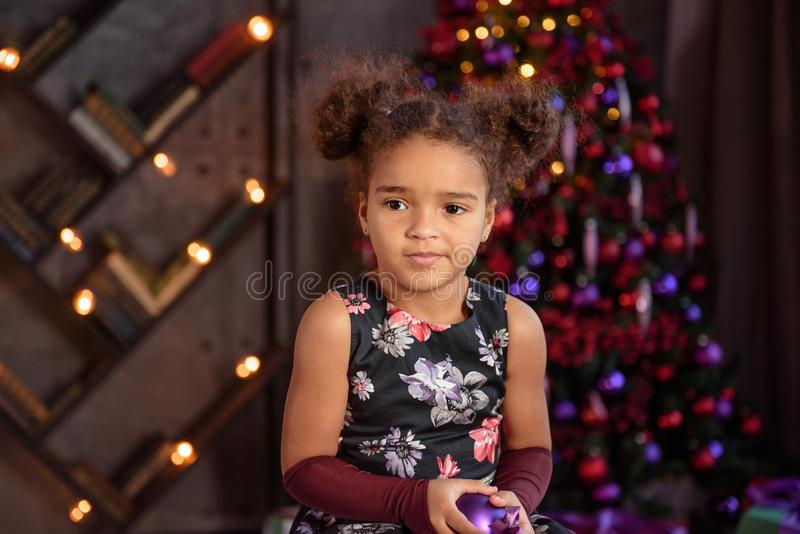 Beautiful kid girl 5-6 year old wearing stylish dress sitting in armchair over Christmas tree in room. Looking at camera. Holiday royalty free stock images