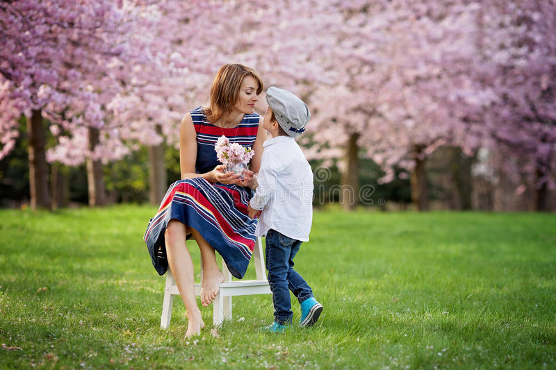 Beautiful kid and mom in spring park, flower and present. Mother. Beautiful kid and mom in cherry blossom spring park, child giving flowers to mother. Mothers royalty free stock photos