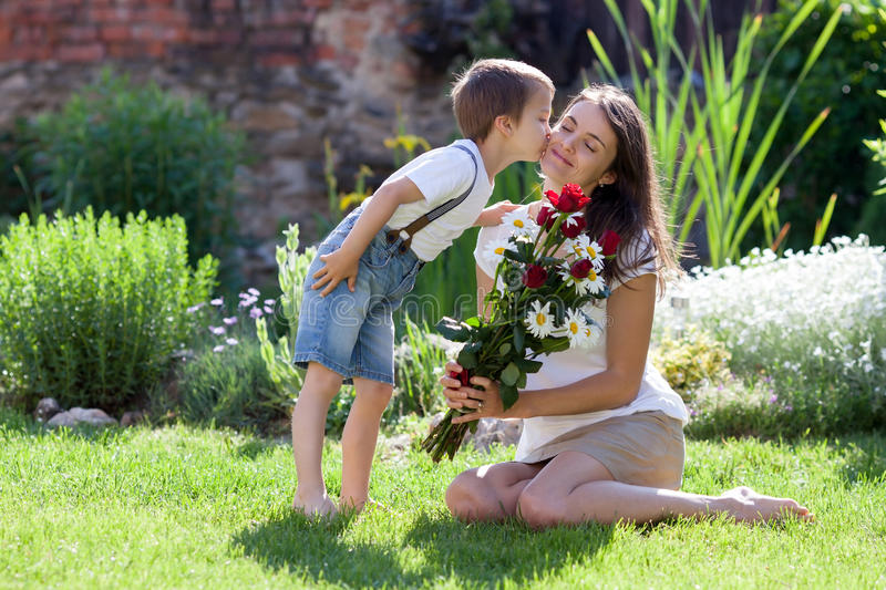 Beautiful kid and mom in spring park, flower and present. Mother. S day celebration concept stock photography