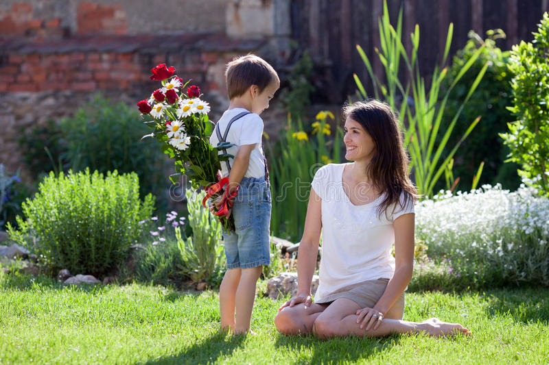 Beautiful kid and mom in spring park, flower and present. Mother. S day celebration concept royalty free stock photos