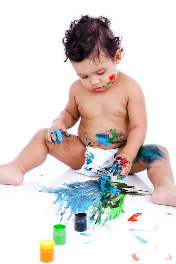 A beautiful kid playing with his paintings. A beautiful kid playing with his paints. The inky boy is busy with his paintings. The toddler is wearing diaper stock photo