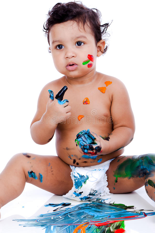 A beautiful kid playing with his paintings. A beautiful kid playing with his paints. The inky boy is busy with his paintings. The toddler is wearing diaper royalty free stock images