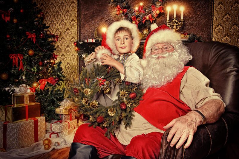 Beautiful kid. Santa Claus in his everyday clothes in Christmas home d�cor. Happy little boy helps Santa Claus get ready for Christmas royalty free stock image
