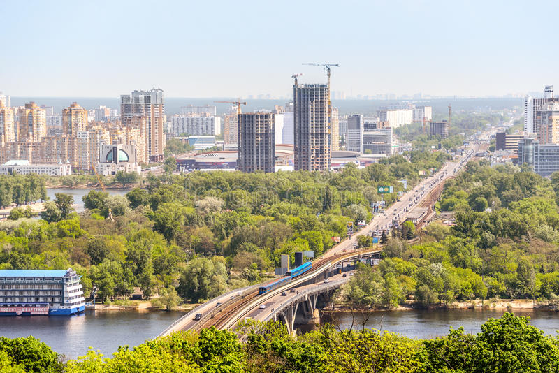 Beautiful Kiev cityscape with bright green trees, river dnepr and buildings on the left river bank. Kiev, Ukraine. Kiev, Ukraine - May 15, 2017: Beautiful Kiev royalty free stock image