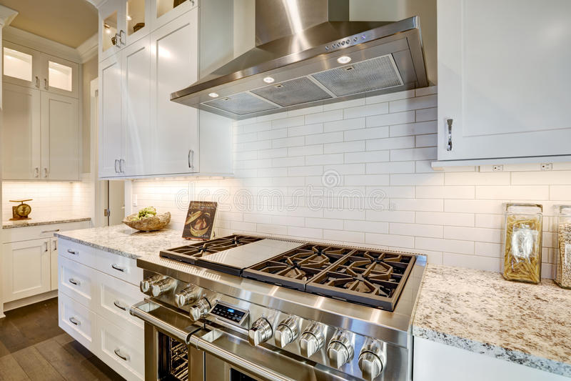 Beautiful kitchen features a nook filled with steel stove. Beautiful kitchen features a nook filled with stainless steel stove, hood, white subway tile stock photo