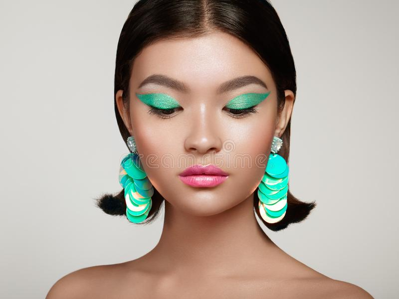 Beautiful Korean Woman with large turquoise earrings. Perfect Makeup and Elegant Hairstyle. Turquoise Make-up Arrows and Pink Lipstick royalty free stock image