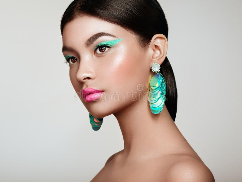Beautiful Korean Woman with large turquoise earrings. Perfect Makeup and Elegant Hairstyle. Turquoise Make-up Arrows and Pink Lipstick stock photo