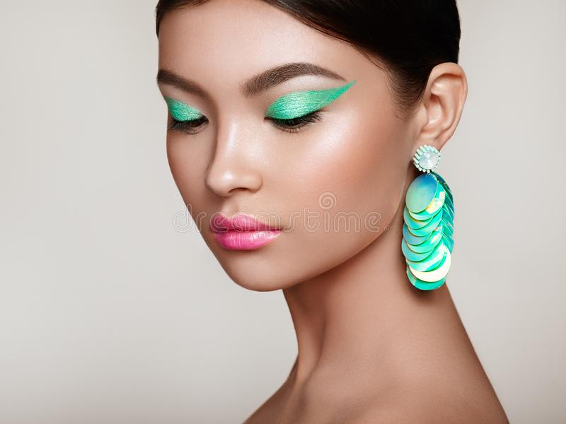 Beautiful Korean Woman with large turquoise earrings. Perfect Makeup and Elegant Hairstyle. Turquoise Make-up Arrows and Pink Lipstick royalty free stock photo