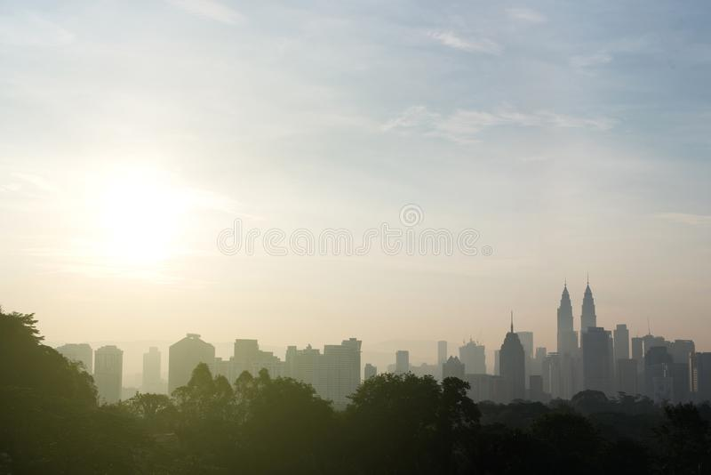 Beautiful kuala lumpur cityscape skyline and surrounding nature with hazy or foggy morning sunshine. Silhouette buildings and trees. nature and development royalty free stock photography
