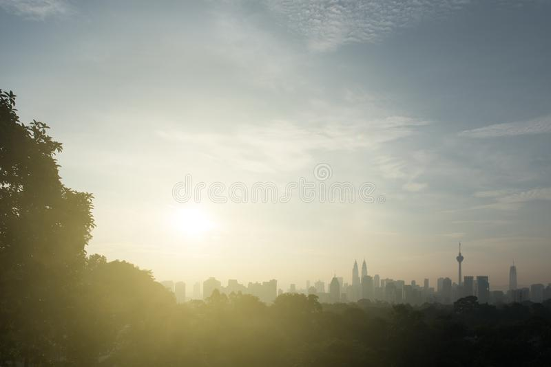 Beautiful kuala lumpur cityscape skyline and surrounding nature with hazy or foggy morning sunshine. Silhouette buildings and trees. nature and development royalty free stock image