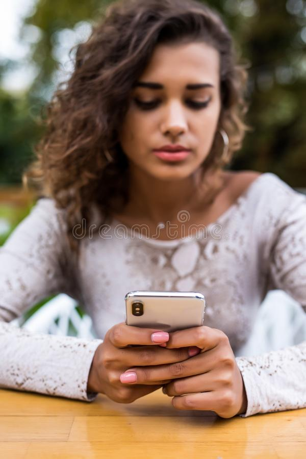 Beautiful l latin girl successful freelancer writes a text message on your phone while sitting in coffee shop. Attractive woman re royalty free stock images