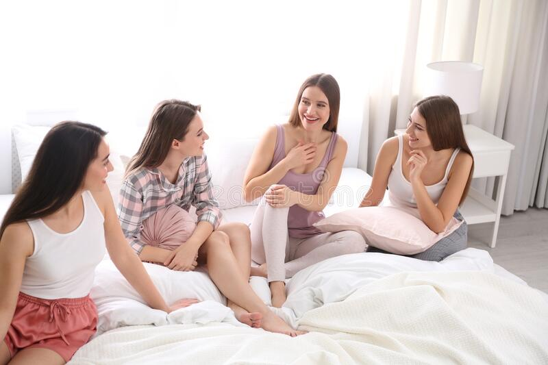 Beautiful ladies on bed at pamper party. Woman`s Day. Beautiful young ladies on bed at pamper party. Woman`s Day stock images