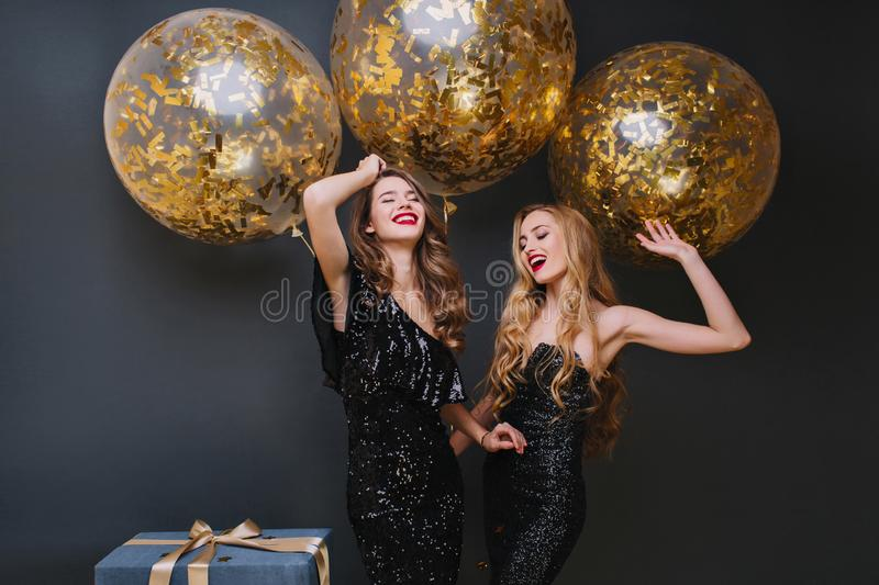 Beautiful ladies dancing with hands up in front of shining helium balloons and smiling. Indoor photo of refined brown royalty free stock photos
